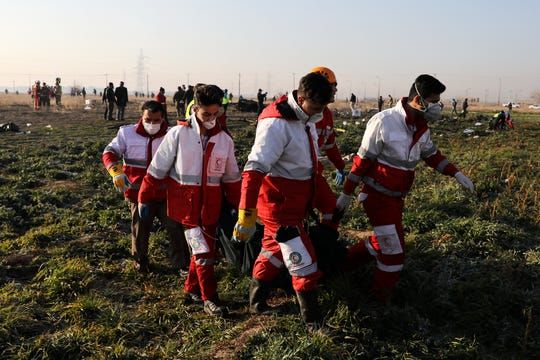 Rescue workers carry the body of a victim of an Ukrainian plane crash in Shahedshahr southwest of the capital Tehran, Iran, Wednesday, Jan. 8, 2020.