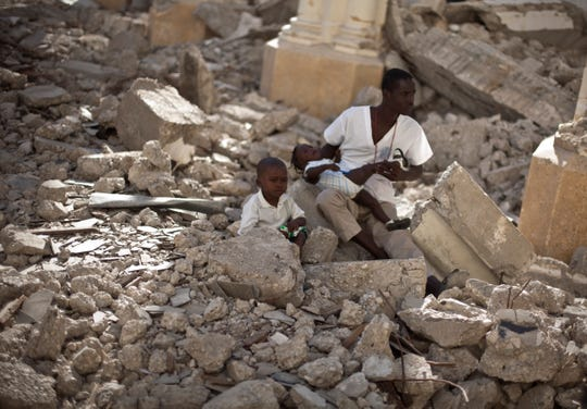A man with two children sits in the rubble of the earthquake damaged Cathedral during a mass in Port-au-Prince, Haiti, Wednesday Jan. 12, 2011.