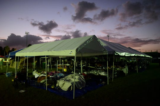 Tents and cots are set up for people whose homes are either destroyed or unsafe to enter after an 6.4 magnitude earthquake, at a baseball stadium amid aftershocks and no electricity in Guayanilla, Puerto Rico, at sunrise Friday, Jan. 10, 2020.