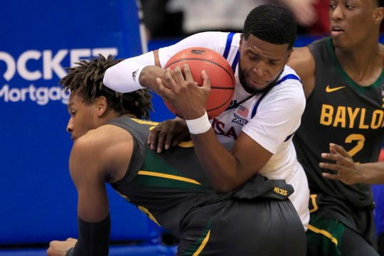 Kansas guard Isaiah Moss, top, rebounds on the back of Baylor forward Freddie Gillespie, left, during the first half.