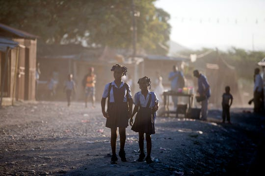 In this Jan. 8, 2020 photo, girls walk to school in Canaan, a district in Croix des Bouquets, Haiti, created for people who lost their homes in the earthquake 10 years ago.