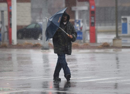 A man struggles with his umbrella along Livernois Avenue at Grand River Avenue as heavy rain and moderate wind hit the Detroit area on Saturday, January 11, 2020.
