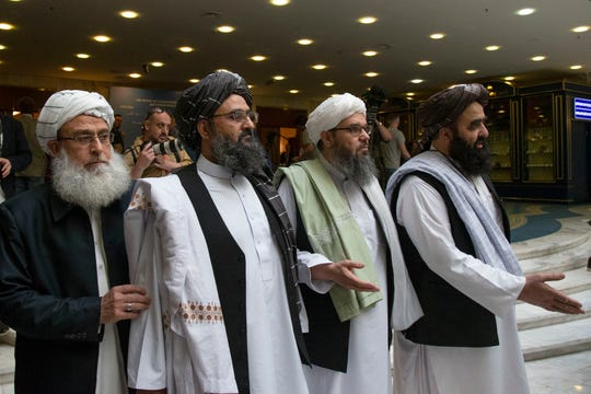 Mullah Abdul Ghani Baradar, the Taliban group's top political leader, second left, arrives with other members of the Taliban delegation for talks May 28, 2019, in Moscow, Russia.