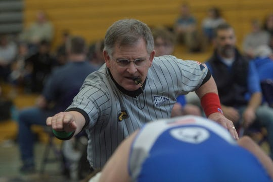 A high school wrestling referee during the Arnold Torgerson Invitational at Fort Collins High School on Saturday, Dec. 11, 2020.