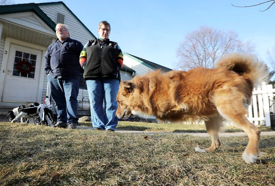 Pete and Pat Sammataro look on as their 4-year-old Australian shepherd mix, Louie, who was born without his two front legs, hops around the front yard at their home in Madison, Wis., on Dec, 27, 2019. UW-Madison engineering students made an adaptive cart for Louie to get around.