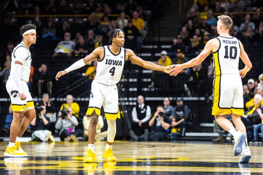 Iowa guard Joe Wieskamp (10) gets a high-five from teammate Bakari Evelyn (4) while settling in on defense after making a 3-point basket as Cordell Pemsl, far left, reacts during a NCAA college Big Ten Conference men's basketball game, Friday, Jan. 10, 2020, at Carver-Hawkeye Arena in Iowa City, Iowa.