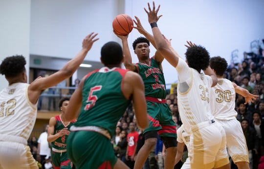 Lawrence North Wildcats Tony Perkins (12) is pressured and has to pass to Lawrence North Wildcats DJ Hughes (5) against the Warren Central Warriors at Warren Central High School on Friday, Jan. 10, 2020.