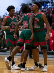 Lawrence North Wildcats' Tony Perkins (12) and Shamar Avance (10) celebrate after a score and foul against the Warren Central Warriors at Warren Central High School on Friday, Jan. 10, 2020.