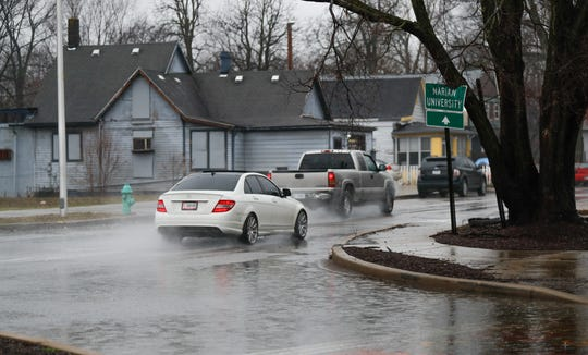 Cars drive through deep puddles just off Michigan St. in Indianapolis, Saturday, Jan. 11, 2020.