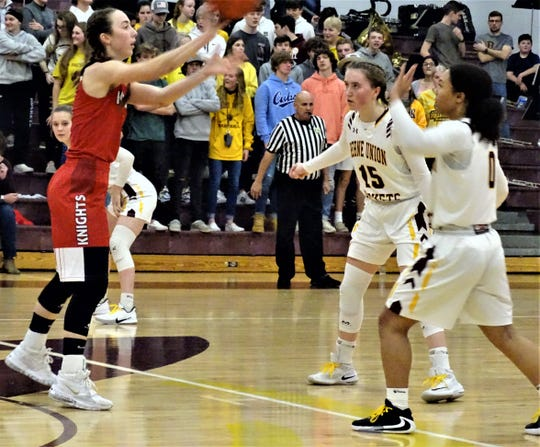 Fairfield Christian Academy's Hope Custer, who finished with 21 points, passes the ball to a teammate while being guarded by Berne Union's Emily Blevins and Abbi Evans.