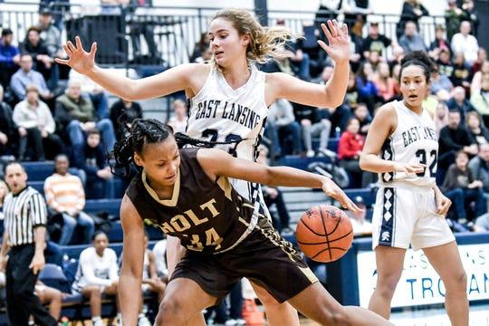 East Lansing's Ella Miller, top, pressures Holt's Janae Tyler during the second quarter on Friday, Jan. 10, 2020, at East Lansing High School.