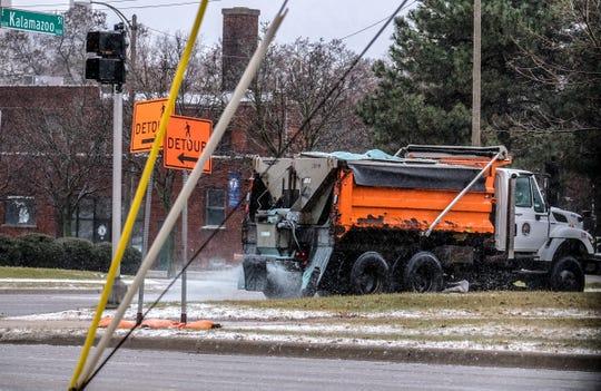A City of Lansing salt truck spreads the ice melting compound along Kalamazoo Street Saturday, Jan. 11, 2020.