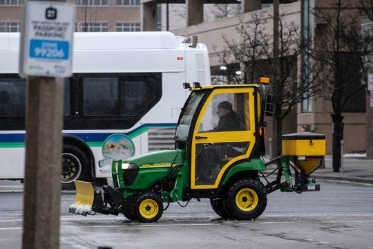 Sidewalks are salted in downtown Lansing as a winter storm covers the area with a slushy mess Saturday, Jan. 11, 2020.