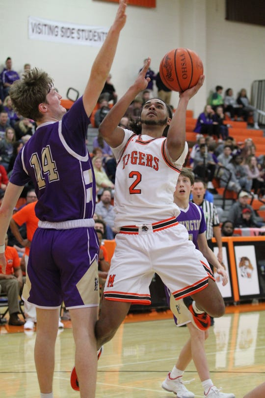 Mansfield Senior's Roger Merrell III drives against Lex's Isaiah Pack in Friday night's Ohio Cardinal Conference basketball game