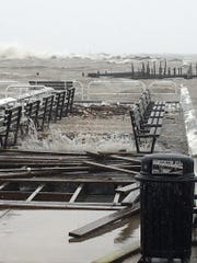 Waves crash through the damaged fishing dock at South Shore Yacht Club. Strong waves brought debris and flooded piers at the Bay View location.