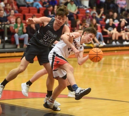 Norfork's Blythe Stapleton is fouled by Izard County's Isaac Jones on Friday night.