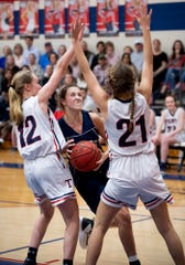 Montgomery Academy's Leighton Robertson (4) is defended by Trinity's Emma Kate Smith (12) and Trinity's Kaylee Peevy (21) on the Trinity campus in Montgomery, Ala., on Friday January 10, 2020.