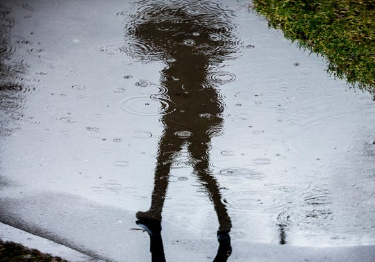 A walker with an umbrella passes a puddle Friday afternoon.