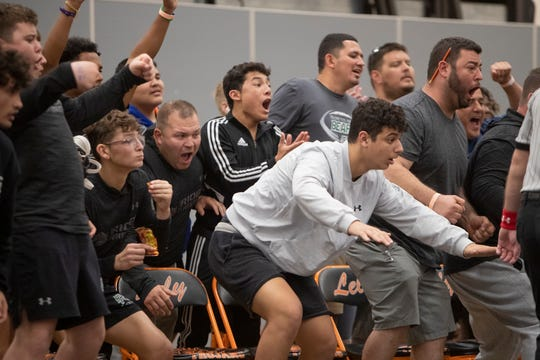 Palmetto Ridge wrestling team cheer on Adrian Ayala as he takes on Barron Collier's Josiah Fernandez in the 138-pound weight class during a wrestling tournament, Saturday, Jan. 11, 2020, at Lely High School.