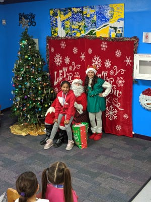 Olivia Hawkins seated on Santa's lap and Santa's helper Yolanda Briseño on the right.