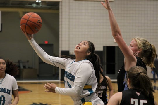 Navajo Prep's Caylynn Lee makes a reverse layup against Sandia Prep during Friday's girls basketball game at the Eagles Nest in Farmington.