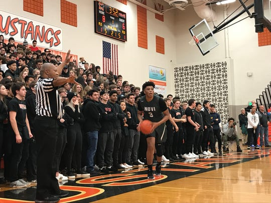 Novi senior forward Bruce Turner tries to throw the ball in in front of the Northville student section