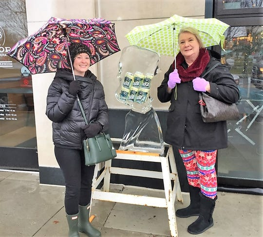Kay and Denise Nikischer of Southgate stand by the melting sculpture in front of the Arbor Brewing Co.