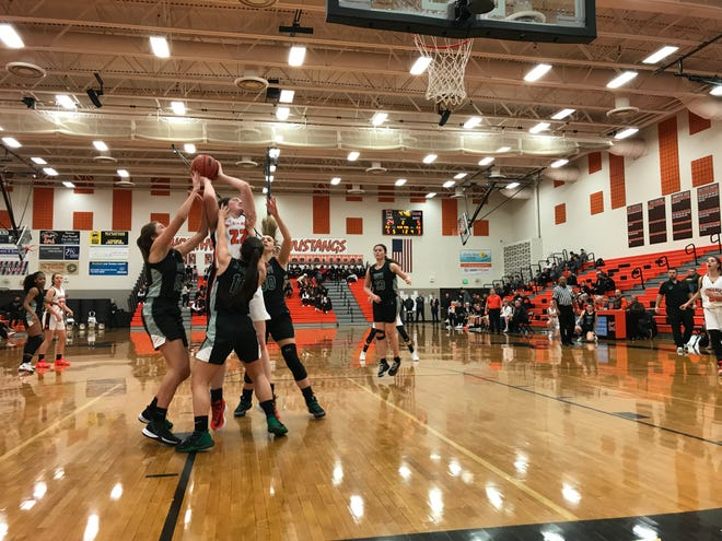 Northville senior forward Morgan Thompson is triple-teamed in the paint against Novi.
