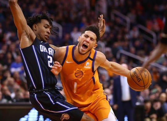 Phoenix Suns guard Devin Booker (1) drives against Orlando Magic forward Wes Iwundu (25) in the first half at Talking Stick Resort Arena on Jan. 10, 2020 in Phoenix, Ariz.
