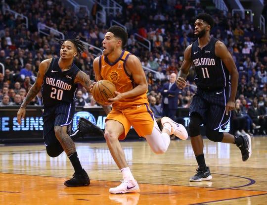 Phoenix Suns guard Devin Booker (1) runs for the basket against Orlando Magic guard Markelle Fultz (20) in the first half at Talking Stick Resort Arena on Jan. 10, 2020 in Phoenix, Ariz.