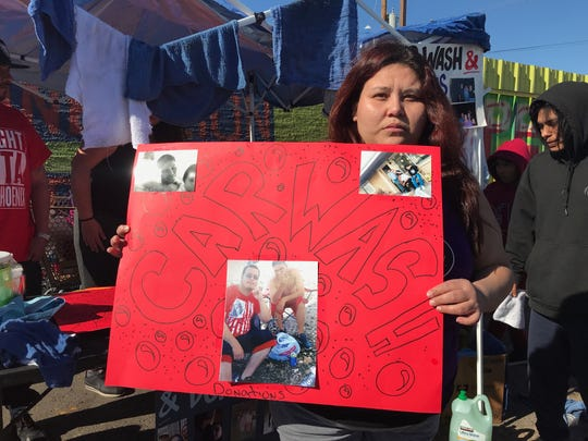 Veronica Rovie holds up a sign with photos of her late brother, Xavier, on Jan. 11, 2020.