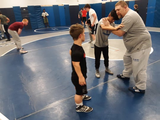 Cedar Crest wrestling coach Chris Voshell instructs Bailey Pennypacker, left, and a teammate during a recent practice.