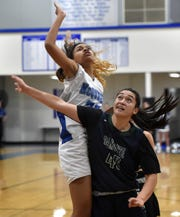 Damonte's Hilinai Smith looks to for the rebound against McQueen's Arizana Peaua during Tuesday night's game at McQueen.