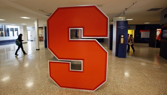 A Syracuse University logo is displayed inside the lobby of the Carmelo K. Anthony Basketball Center.