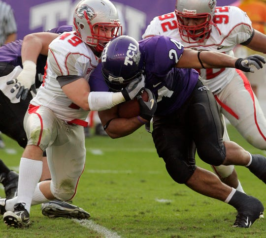 New Mexico linebacker Zach Arnett (49) stops TCU tailback Joseph Turner (24) in the first quarter of a football game in Fort Worth, Texas, on Saturday, Nov. 3, 2007. Arnett amassed 200 tackles, four sacks and six forces fumbles during his playing days with the Lobos.