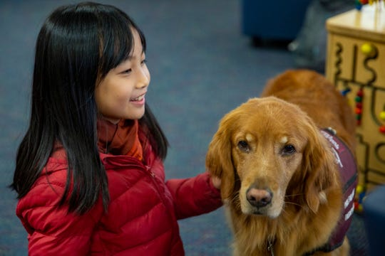 Meng Meng, 9, of Monmouth, pets the therapy dog Lexie at the Salem Public Library on Jan. 11, 2020.