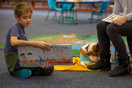 Dennis Dreischmeyer, 9, of Keizer, reads to the therapy dog Tucker at the Salem Public Library on Jan. 11, 2020.