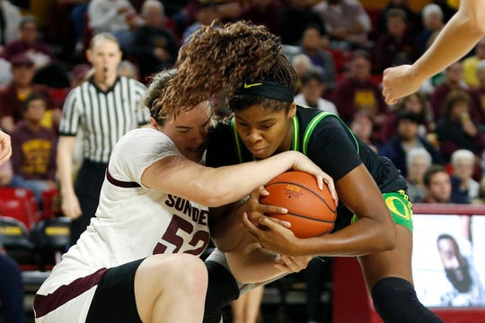 Arizona State center Jamie Ruden (52) and Oregon forward Ruthy Hebard compete for possession of the ball during the first half of an NCAA college basketball game Friday, Jan. 10, 2020, in Tempe, Ariz.