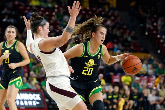 Oregon guard Sabrina Ionescu (20) collides with Arizona State's Robbi Ryan as she drives to the basket during the first half of an NCAA college basketball game Friday, Jan. 10, 2020, in Tempe, Ariz.