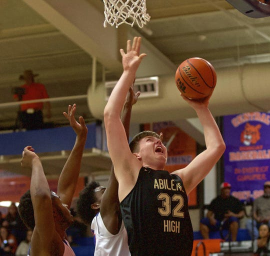 Nathan Watts, center, lays the ball in for Abilene during a game against Central in San Angelo on Friday, Jan. 10, 2020.