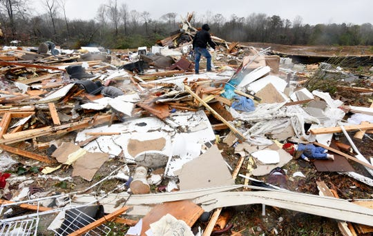 A family member of a south Bossier, Louisiana, couple killed in overnight storms searches through the remains of the home on Saturday, Jan. 11, 2020, for salvageable items.