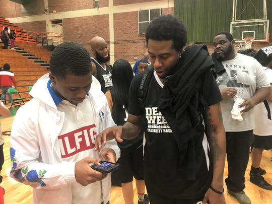 "Streetball legend Philip ""Hot Sauce"" Champion (right) shows Demarkus Solomon of Tallahassee his social media info following a celebirty basketball game inside the Gaither Gymnasium for Demp Week 23 on Friday, Jan. 10, 2020."