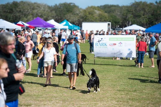 A proposed ordinance would clarify where leashed dogs can walk with their owners, including at some beach areas. In this photo taken Jan. 11, 2020, Holli Kozar (left) and Jim Kozar walk with Opie, a border collie, at the seventh annual Bark in the Park at Riverside Park in Vero Beach.
