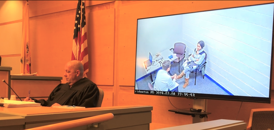 Cumberland County Superior Court Judge Robert Malestein takes notes during a suppression hearing on Friday in the Nakira Griner case. Griner is charged with killing her 23-month-old son in February 2019. Her interview with a state police detective prior to arrest plays on a screen behind the judge.