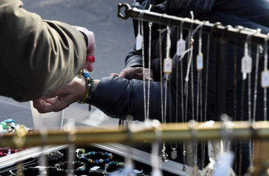 Visalia Farmers Market merchant Alicia Post snips the tag off a purchased bracelet at her booth on Saturday, Jan. 11.