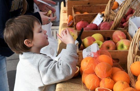 A boy inspects an apple at the Visalia Farmers Market on Saturday, Jan. 11.
