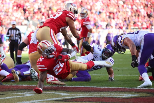 San Francisco 49ers running back Tevin Coleman (26) scores a touchdown against the Minnesota Vikings in the second quarter in a NFC Divisional Round playoff football game at Levi's Stadium.