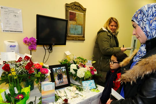 Khadija Sqalli, a patient of Dr. Shekoufeh Choupannejad, looks at a memorial at her office on Jan. 9, 2020 in Edmonton, Canada. Choupannejad, who along with her two daughters, Sara and Saba, were victims on the Ukraine International Airlines flight that crashed in Iran.