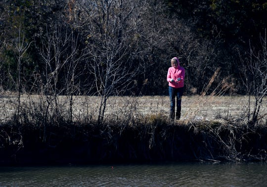 woman fishes for trout on the bank opposite Cal Young Park during Saturday's Trout Fest.
