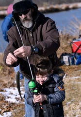 Elliot Johnson, 5, holds his rod as his great-uncle Mike steadies his fish.